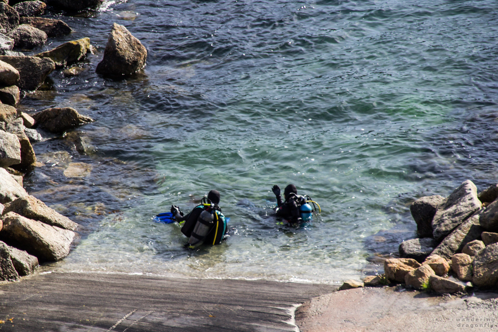 Scuba divers enter the water at Whalers Cove -- ocean, rock, scuba diver, water