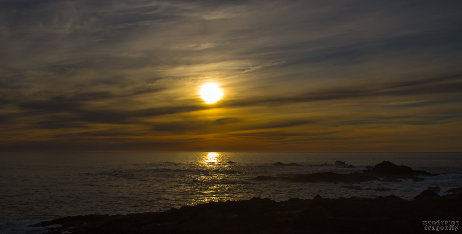 Beginning of the sunset at Sea Lion Point -- cliff, cloud, ocean, rock, sun, sunset, water