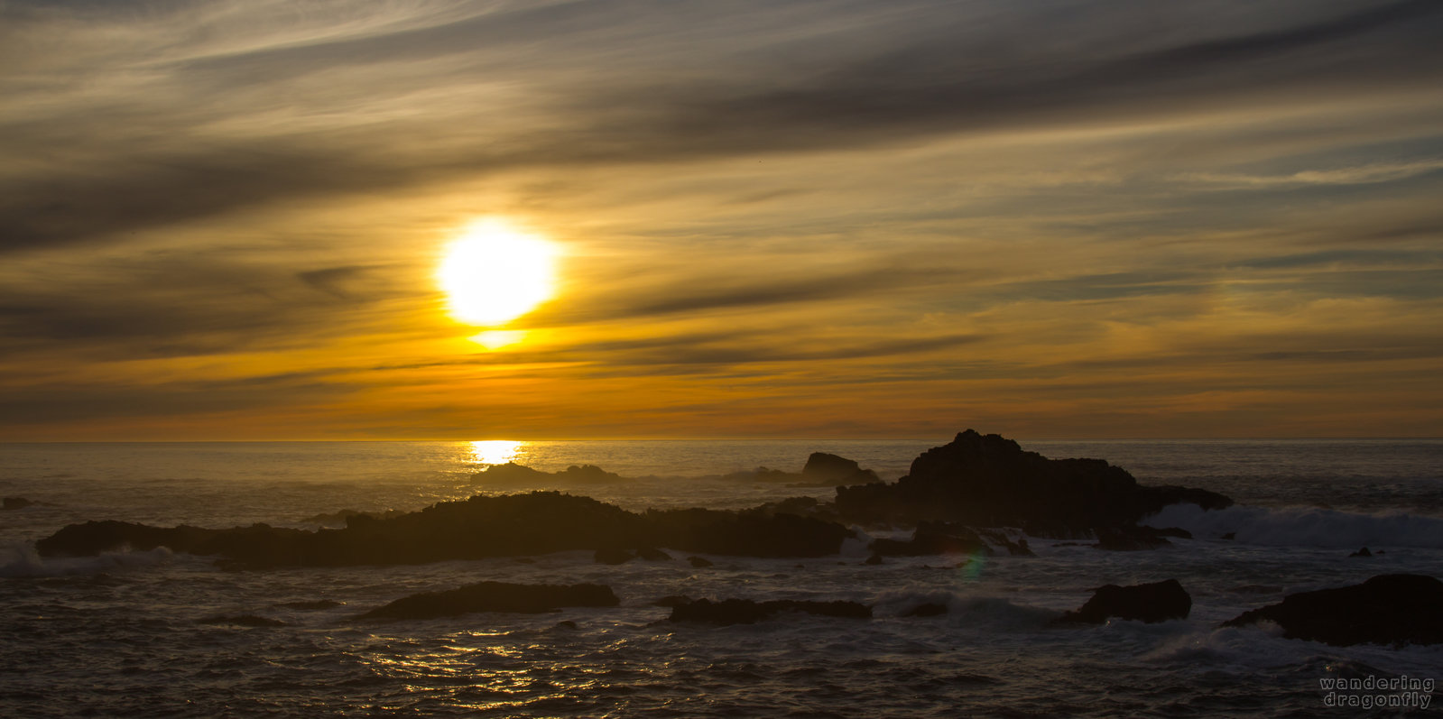 Blurred descending sun -- cloud, ocean, rock, sun, sunset, water, wave