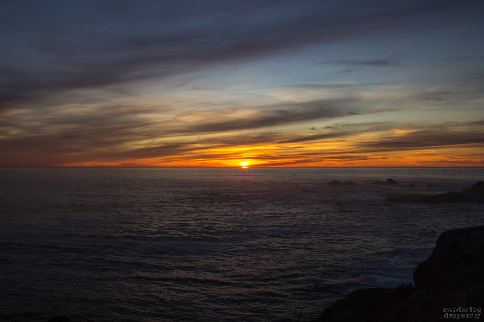 Last wink of the sun -- cloud, ocean, rock, sun, sunset, water, wave