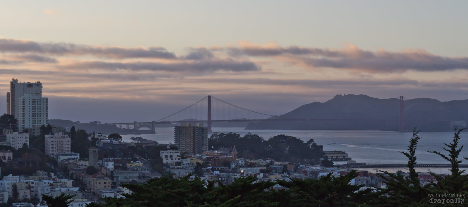 The Golden Gate Bridge at twilight as seen from the Coit Tower -- bridge, building