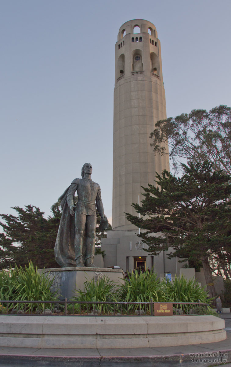 Picture of the Coit tower with the statue of Columbus in the foreground -- statue, tower